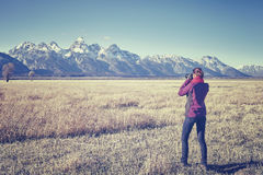 Vintage toned female fit hiker taking pictures with DSLR camera Stock Photography