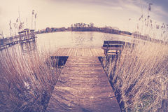 Vintage toned fisheye lens image of a wooden pier. Royalty Free Stock Photography