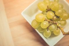 Grape in white bowl on wooden table. Vintage toned grapes in white bowl on wooden table Stock Photography