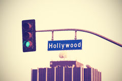 Vintage toned Hollywood street sign and traffic lights, LA, USA. Royalty Free Stock Images