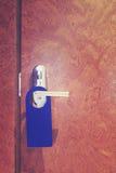 Vintage toned hotel room closed door with hanger. Stock Image