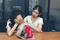Vintage toned image of attractive Asian woman comforting a sad depressed female friend. Break up or best relationship concept. Royalty Free Stock Images