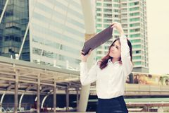 Vintage toned image of attractive business woman raises office document folder to shield from sunlight at street city. stock photography