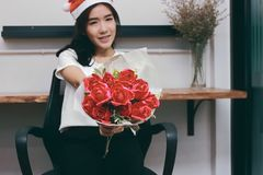 Vintage toned image of attractive young Asian woman in Santa hats holding a bouquet of red roses in office. royalty free stock photos