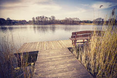 Vintage toned image of a bench on wooden pier. Royalty Free Stock Images