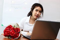 Vintage toned image of cheerful young Asian business woman with a bouquet of red roses on the desk in office. Valentine`s day con Stock Photos