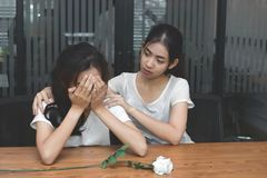 Vintage toned image of frustrated stressed Asian woman comforting a sad depressed female friend. Break up or best relationship con Stock Photos