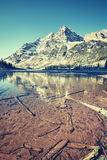 Vintage toned Maroon Bells reflected in frozen lake, Colorado, U Royalty Free Stock Photography