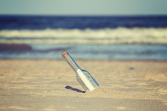 Vintage toned message in a bottle on beach. Royalty Free Stock Image