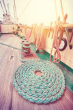 Vintage toned mooring rope on wooden deck. Royalty Free Stock Images