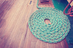 Vintage toned mooring rope on wooden deck. Royalty Free Stock Image