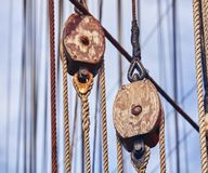 Vintage toned old sailing ship wooden pulleys. stock photo