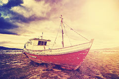 Vintage toned old ship on a beach at sunset. Stock Photo