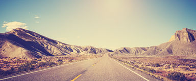 Vintage toned panoramic photo of desert road. Royalty Free Stock Photo