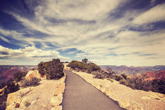 Vintage toned path to the Grand Canyon South Rim viewpoint. Stock Photos