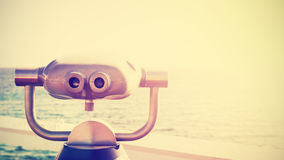 Vintage toned photo of a binocular pointed at horizon. Stock Photos