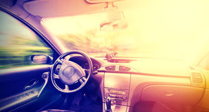 Vintage toned picture of a driving car interior. Royalty Free Stock Photography