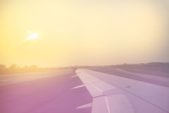Vintage toned plane wing above runway at sunrise Royalty Free Stock Image