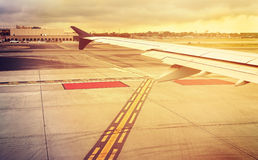 Vintage toned plane wing above runway at sunset. Royalty Free Stock Photo