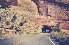 Vintage toned road through rock tunnel, Colorado, USA. Stock Photo