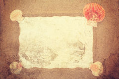 Vintage toned sea shells with sand and white paper as background Royalty Free Stock Photo