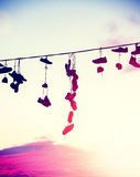Vintage toned silhouettes of shoes hanging on cable at sunset. Stock Photos