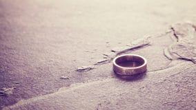 Vintage toned single weeding ring on stone background. Royalty Free Stock Photo