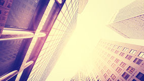 Vintage toned skyscrapers against sun, lens flare effect. Royalty Free Stock Photos