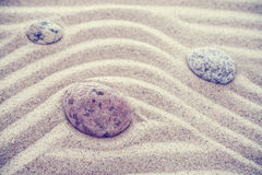 Vintage toned stones on sandy waves, nature and harmony concept Royalty Free Stock Photo