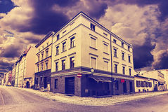 Vintage toned street corner withe rainy clouds. Royalty Free Stock Photo
