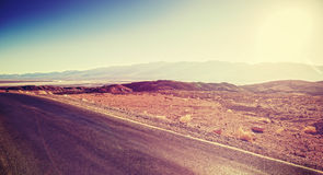 Vintage toned sunset over desert road, travel background Stock Images
