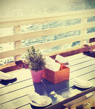 Vintage toned table setting on pier at sunset. Stock Image