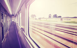 Vintage toned train window with blurred rails outside. Stock Photo