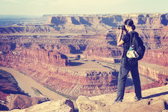 Vintage toned woman taking pictures of a canyon landscape, USA Royalty Free Stock Images