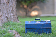 Vintage toolbox in grass. Vintage metal blue toolbox in grass under tree Stock Image