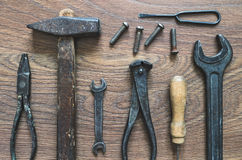 Vintage tools on wooden background. Different tools (pliers, hammer, awl, wrench, nippers, chisel) on a wooden background Stock Photos