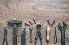 Vintage tools on wooden background. Different tools (pliers, hammer, awl, wrench, nippers, chisel) on a wooden background Royalty Free Stock Photos