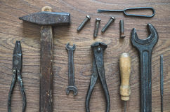 Vintage tools on wooden background. Different tools (pliers, hammer, awl, wrench, nippers, chisel, rasp, screwdriver) on a wooden background Royalty Free Stock Photo