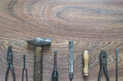 Vintage tools on wooden background. Different tools (pliers, screwdriver, hammer, rasp, awl) on a wooden background Stock Photography