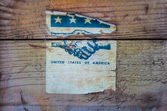 Vintage torn label of the United States of America. On wood with stars and stripes and shaking hands Stock Photography