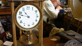 Vintage torsion pendulum clock on table while horologist working in background stock video footage