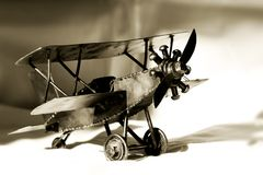 Vintage Toy Bi-Plane (sepia). A vintage, toy metal bi-plane in shadow and light (sepia tone, shallow focus) - can represent travel and history stock image