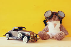 Vintage toy car and cute teddy bear on wooden table Royalty Free Stock Photos
