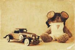 Vintage toy car and cute teddy bear on wooden table Stock Photos