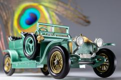 Vintage toy car macro with peacock train feather background stock images