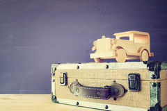 vintage toy car and old suitcase on wooden table Stock Image