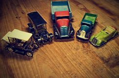 Vintage toy cars lorry truck and convertible car  on brown wooden background. Retro toys for boys. Flat design with blank and Royalty Free Stock Image