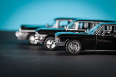 Vintage toy cars standing sideways. On blue background Royalty Free Stock Images