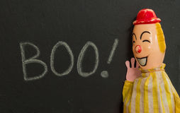 Vintage toy clown shouting BOO. Chalk on slate. Boo! Chalk text on slate with creepy vintage toy clown. Clown appears to be very happy to have scared someone royalty free stock photo
