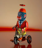 A vintage toy - Monkey over a tricycle. An antique windup toy showing a monkey with a red suit pedaling in his tricycle Royalty Free Stock Images